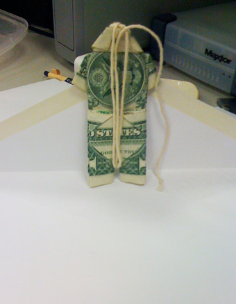Two bills shaped like a shirt and pants hanging on a string.
